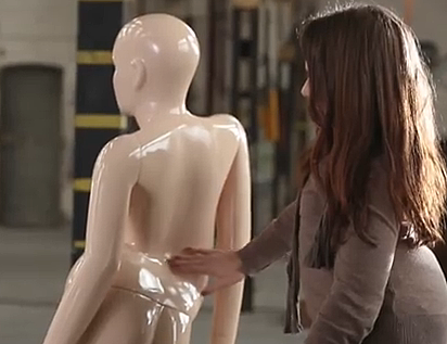 A disabled woman looks over her mannequin.